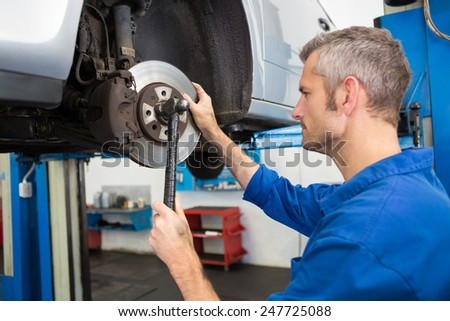 Focused mechanic adjusting the wheel at the repair garage - stock photo