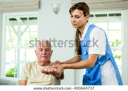 Focused nurse assisting senior man at health club