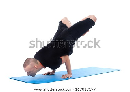 Focused on sporty man posing in complex yoga pose