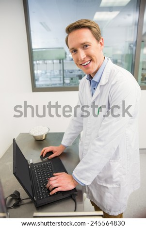 Focused pharmacist using his laptop at the hospital pharmacy