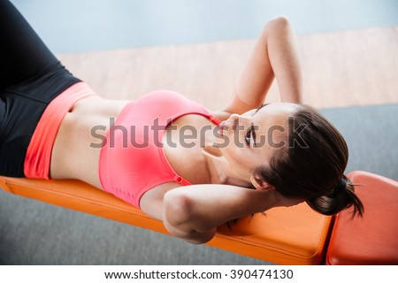 Focused pretty young sportswoman doing abs crunches on bench in gym  - stock photo
