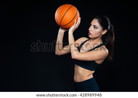 Focused pretty young woman athlete standing and throwing basketball ball over black background