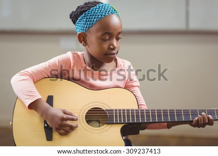Focused pupil playing guitar in a classroom in school