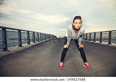 Focused runner outdoors resting on the bridge - stock photo