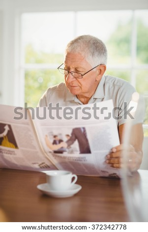 Focused senior man reading newspaper at home
