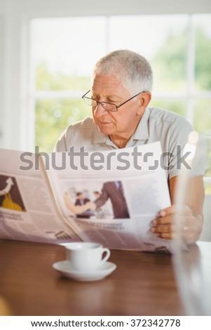 Focused senior man reading newspaper at home - stock photo