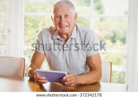 Focused senior man using tablet at home - stock photo