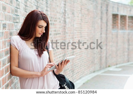 Focused student using a tablet computer outside a building