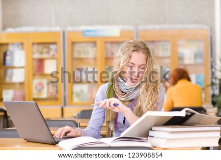 focused student using computer in a library - stock photo