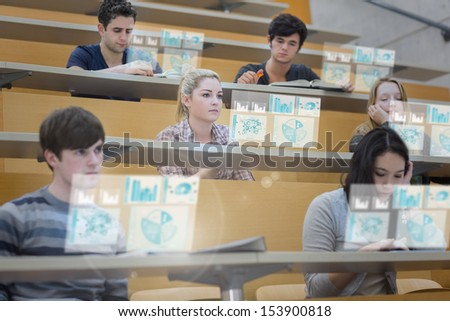 Focused students in lecture hall working on their futuristic tablet during lesson - stock photo