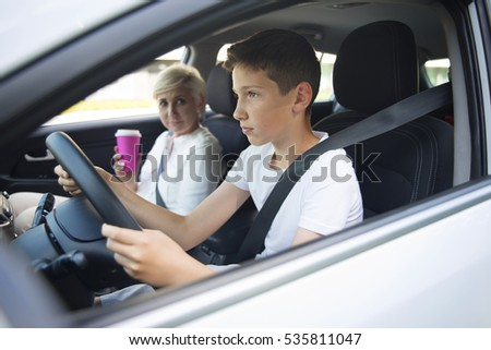 Focused teenager learning to drive a car with his mother