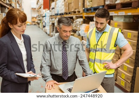 Focused warehouse team working together on laptop in a large warehouse