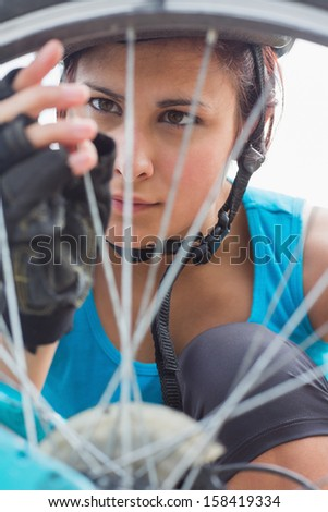 Focused woman adjusting her spokes on bike wheel in the countryside - stock photo