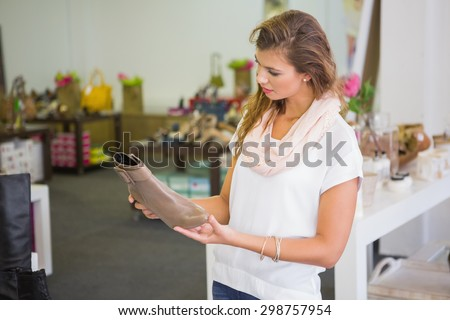 Focused woman looking at ankle boots at a shoe store