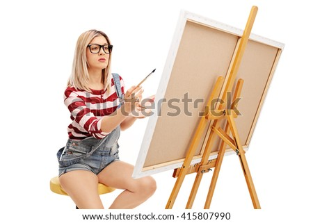 Focused woman painting on a canvas with a paintbrush isolated on white background - stock photo