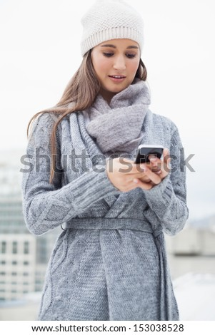 Focused woman with winter clothes on text messaging outdoors on a cold grey day - stock photo
