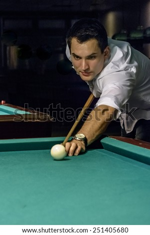 focused young male billiard player - stock photo