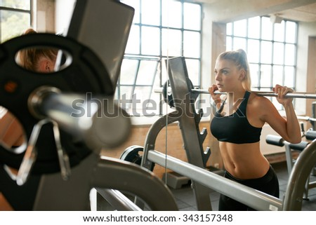 Focused young woman lifting weights in health club. Woman doing squats in front of mirror in gym. - stock photo