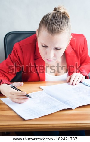 Focused young woman reading documents at her desk.