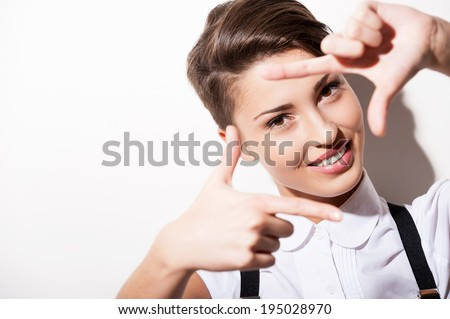 Focusing at you. Beautiful young short hair woman in white shirt and suspenders focusing at you with finger frame - stock photo
