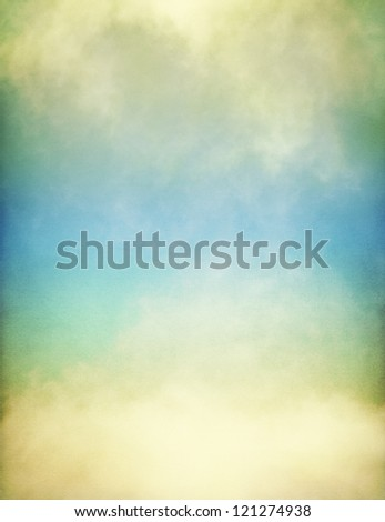 Fog and clouds on a vintage, textured paper background with a colorful yellow to blue gradient.  Image displays a pleasing paper grain at 100%. - stock photo