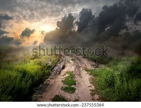 Fog and dirt over country road at sunset - stock photo