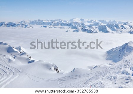 Fog and mist above in the valley at winter in snow covered mountains - stock photo