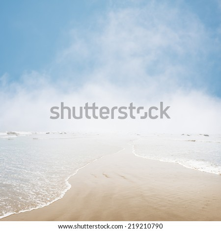Fog and mist hovering on the ocean horizon with gentle waves overlapping in the foreground. - stock photo