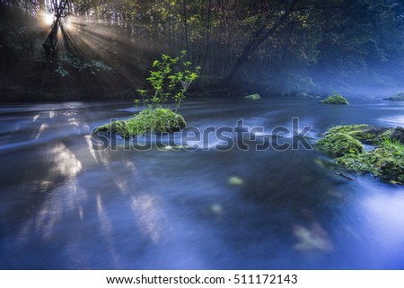 Fog and sun breaking at the river. Radiant, morning sun and backwashing mist during long exposure, summer at river and sliding water, sunny backlight and fog with running water