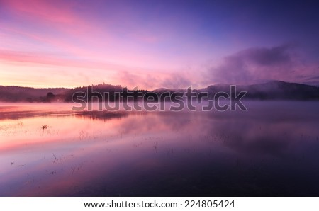 Fog at dawn over Lake Solina in the Bieszczady Mountains - stock photo