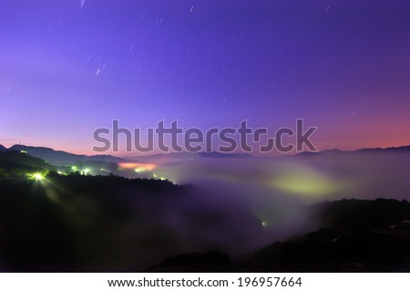 Fog bank rolling in on hills during dusk. - stock photo