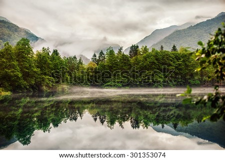 fog creeps over the water of Lower Blue Lake, Kabardino-Balkaria Republic - stock photo