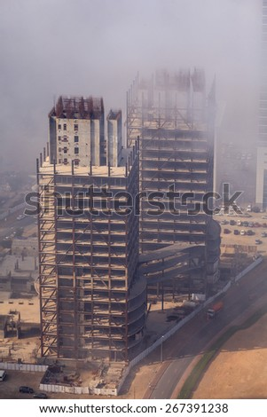 Fog has covered a building under construction in Business bay, Dubai. - stock photo