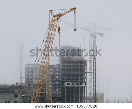 fog hid the construction site with cranes