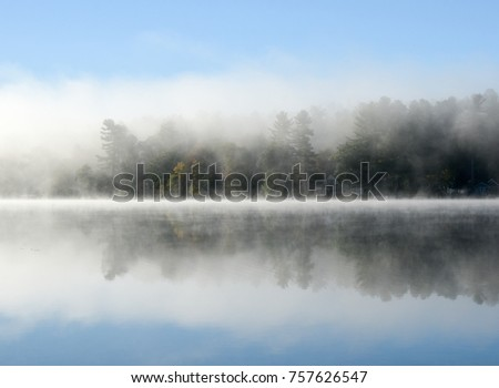 Fog in early morning drifts across a lake. The cloud of fog rests on the water and reflects back in it creating dual image of the cloud. Soft and moody.