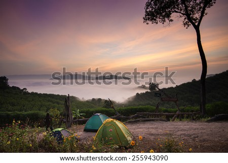 Fog in mountain before sunrise and tents of traveller - stock photo