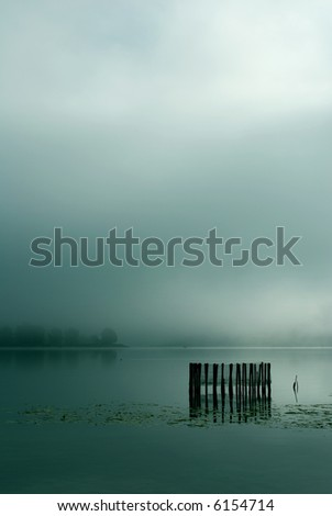Fog on lake early in the morning - stock photo