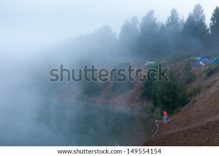 Fog on the lake with standing tourist tents - stock photo