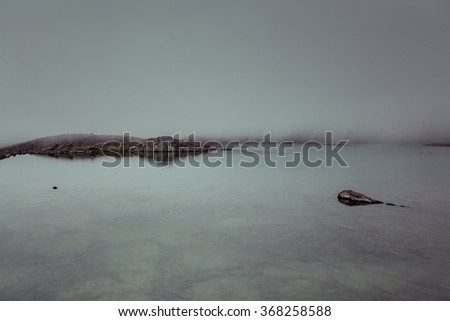 Fog on the mountain lake with a floating stone.?alming serenity.