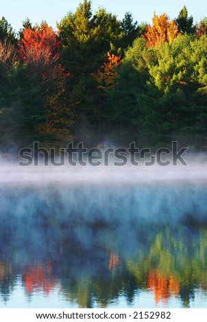 Fog on the water in the morning, with autumn trees reflecting. - stock photo