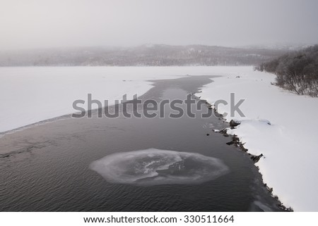 fog over a frozen river in sweden - stock photo
