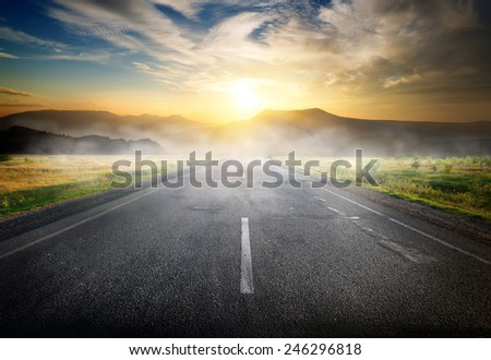 Fog over highway to mountains at sunrise - stock photo