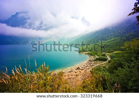 Fog over lake in mountains. Fantasy and colorfull nature landscape. Nature conceptual image. Morskie Oko in Tatry, Poland. - stock photo
