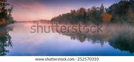 Fog over the lake at dawn. Wooded shores. Indian summer. Horizontal panorama.