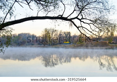 Fog over the water. The morning landscape with fog and warm sky - stock photo