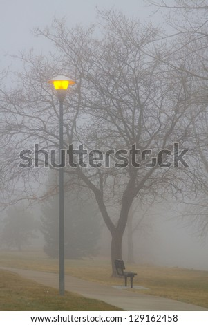 Fog, park bench and street light view. Portrait image, Colorado fog set in and hung around late morning setting the mood in the park. - stock photo