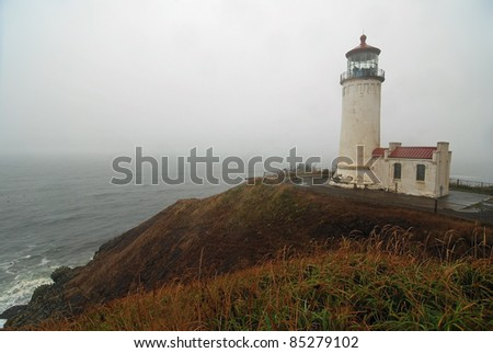 Fog rolling in over Pacific Coast of Washington veils North Head Lighthouse on Cape Disappointment State Park.
