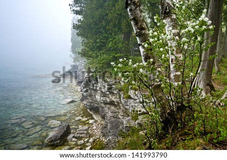 Fog rolls in along the rocky shoreline of Cave Point County Park in Door County, Wisconsin. - stock photo