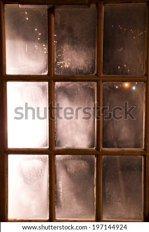Fogged window with nine small rectangular panes in wooden frame. - stock photo