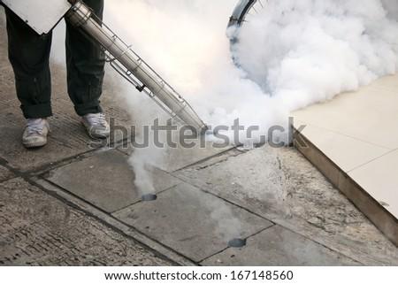 Fogging into the drain to prevent spread of dengue fever - stock photo